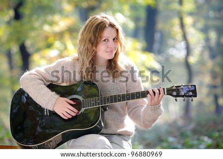 Young Caucasian girl in  forest with guitar, selective focus