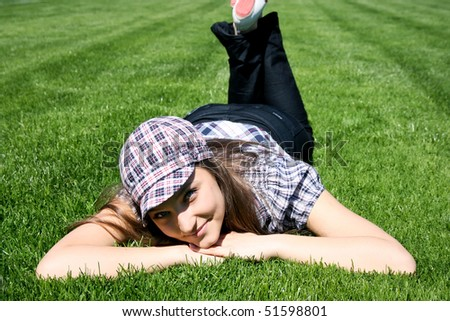 Young caucasian girl lays on the green grass