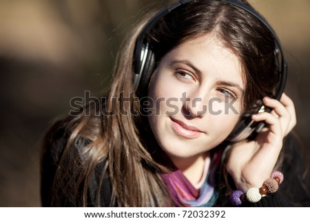 Young caucasian girl listening to music with headphones looking aside