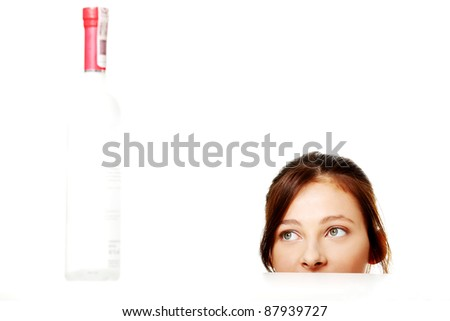 Young caucasian girl looking at the bottle with alcohol. - stock photo