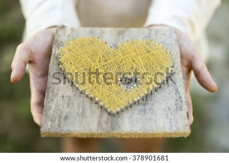 Young caucasian girl offering symbolic heart  open palms - stock photo