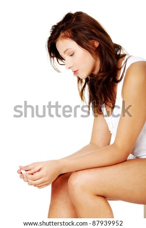 Young caucasian girl sitting and checking her pregnant test. - stock photo
