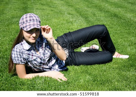 Young caucasian girl sitting on the green grass