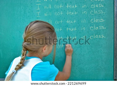 young Caucasian girl student writing lines on green chalkboard - stock photo