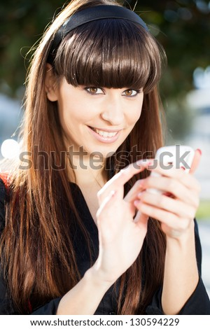 Young Caucasian Girl Text Messaging In The Park, Smiling, Looking At The Camera. - stock photo