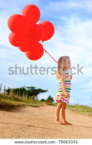 Young caucasian girl walks along a path, holding a bunch of helium filled red balloons