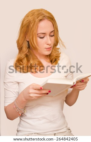 young caucasian girl wearing white t-shirt reading book isolated on white background - stock photo