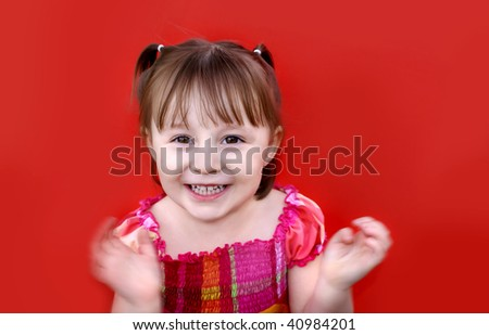 Young caucasian girl (2 years old) in pigtails wearing a red and pink plaid dress smiles and claps her hands in excitement. Shot against a red backdrop. - stock photo