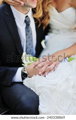 young caucasian groom and bride holding hands - stock photo