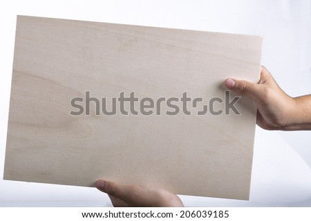 Young caucasian hands holding a light color plywood square blank signboard with shadow  on white background. There are no elements to distract viewer from reading any  message written on the sign - stock photo
