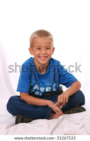 Young caucasian lad with blonde hair and big smile sitting with legs crossed