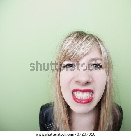 Young Caucasian lady clenches her teeth over green background - stock photo