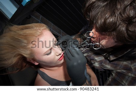 Young Caucasian lady gets her lip pierced by tattoo artist - stock photo