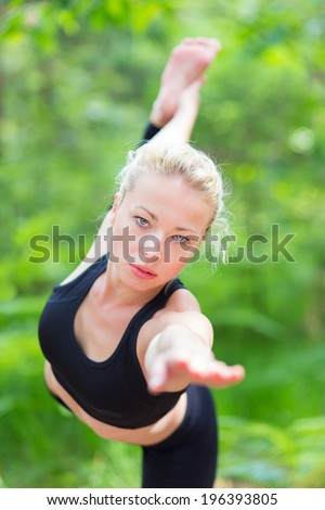 Young caucasian lady is practicing bikram yoga pose in the nature. - stock photo