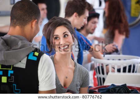 Young Caucasian lady with boyfriend grins in laundromat - stock photo