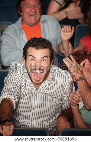 Young Caucasian laughs out loud in theater - stock photo