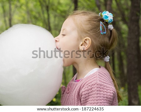 Young caucasian little girl eating big white cotton candy in the park outdoor - stock photo