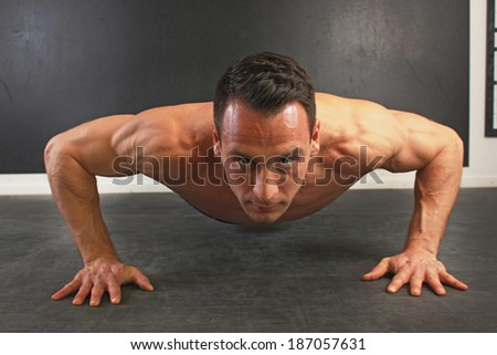 Young caucasian male doing push ups. Front view. - stock photo