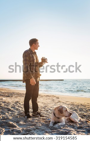 young caucasian male drinking coffee on beach while walking with dog during sunrise - stock photo
