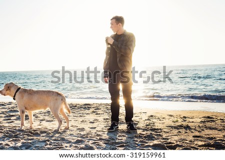 young caucasian male drinking coffee on beach while walking with dog during sunrise