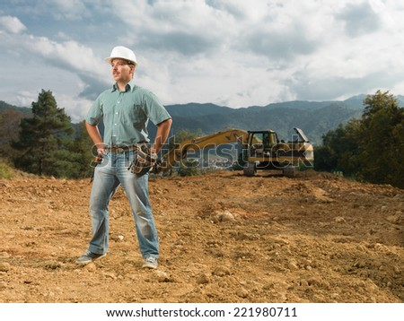 young caucasian male engineer standing on construction site, with excavator in background