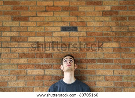 Young caucasian male looks up above his head leaning against a brick wall. - stock photo
