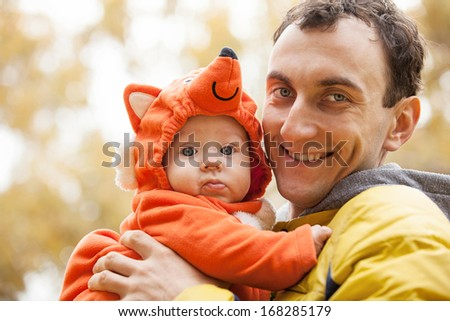 Young Caucasian man and his little son in fox costume in autumn park  - stock photo