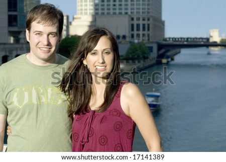 Young Caucasian man and woman posingÃ?with water in background. - stock photo
