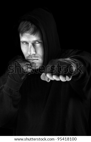 Young caucasian man boxing; isolated on black background