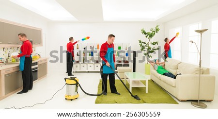 young caucasian man cleaning home in different places at the same time while wife rests on sofa - stock photo