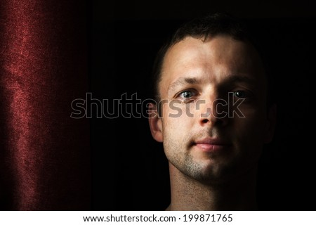 Young Caucasian man close up portrait with curtain - stock photo