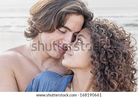 Young Caucasian man closely embraces young pretty Hispanic woman while gazing into each others eyes on beautiful beach - stock photo