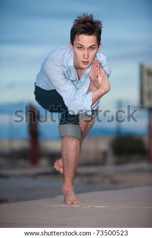 Young Caucasian man crouches on one leg for yoga exercises outdoors - stock photo