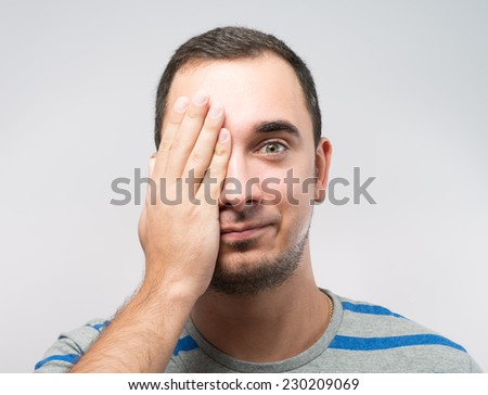 Young Caucasian man hiding his eye with hand - stock photo