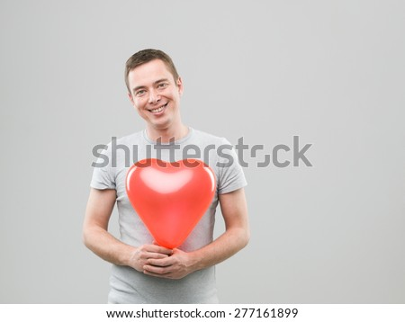 young caucasian man holding heart shaped balloon and smiling. copy space available - stock photo