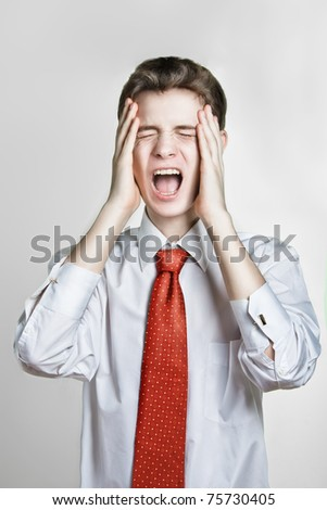 Young caucasian man in a shirt with red tie, screaming and hold his head, isolated.