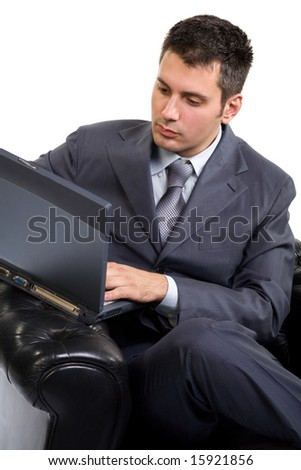Young caucasian man in a suite, sitting in armchair working on laptop