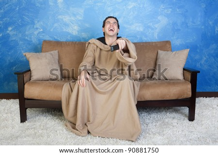 Young Caucasian man in blanket with remote control laughs out loud - stock photo