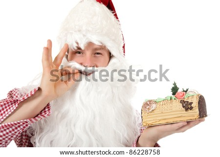Young caucasian man in Santa Claus clothes gesturing tasty for the christmas cake with moca cream and biscuit doug. Studio shot. White background. - stock photo