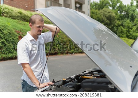 Young caucasian man is thinking about how to repair his car - stock photo