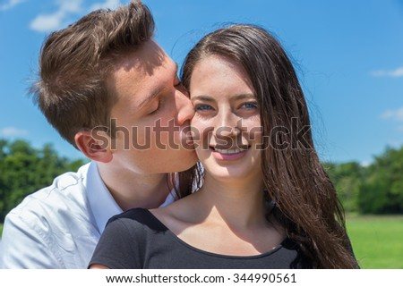 Young caucasian man kisses attractive girl on forehead against blue sky - stock photo