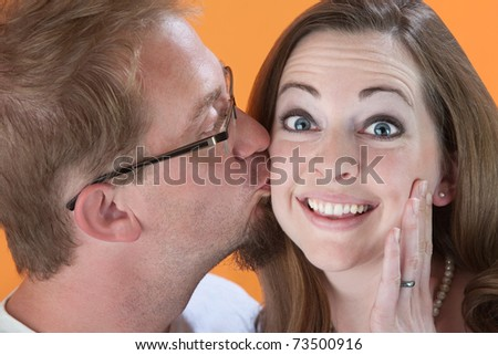 Young Caucasian man kissing young woman on her cheek - stock photo