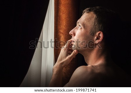 Young Caucasian man looking in the window, closeup profile portrait