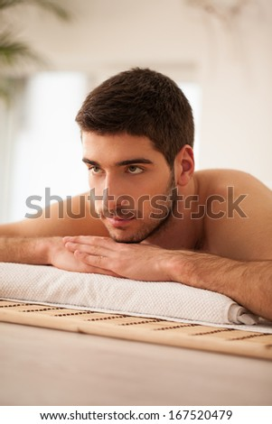 Young Caucasian man lying on the massage table and waiting for a massage.