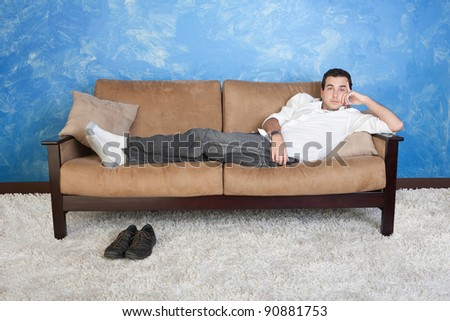 Young Caucasian man rests on sofa with shoes on floor - stock photo