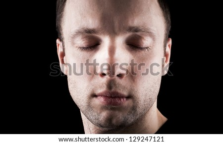 Young Caucasian man's portrait with closed eyes above black background - stock photo