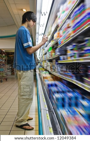 Young Caucasian man shopping in a supermarket - stock photo
