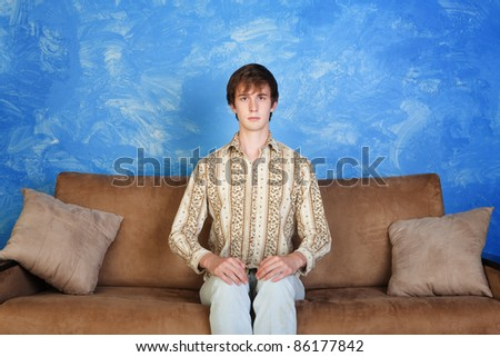 Young Caucasian man sits straight on sofa