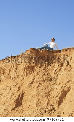 young caucasian man sitting alone over the rock - stock photo