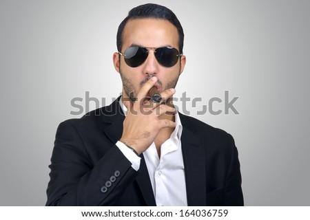 Young Caucasian man smoking cigar  - stock photo